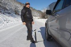 膨胀汽车的轮胎 人汽车修理在森林里,冬天 汽车抽的空气到轮子里 人使用一个气汞 抽的a 库存图片
