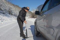 膨胀汽车的轮胎 人汽车修理在森林里,冬天 汽车抽的空气到轮子里 填装的空气到一个脏的车胎里 库存图片