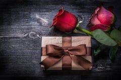 膨胀的玫瑰包裹了在木委员会的当前箱子 免版税库存图片