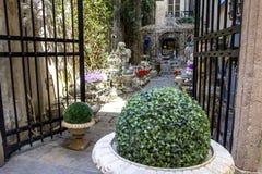 膨胀的门被邀请在一个舒适,美丽的庭院里参观 免版税库存图片