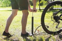膨胀轮胎的自行车 骑自行车者修理在森林自行车骑士抽的空气的自行车入轮子 骑自行车的人使用一个气汞 库存照片