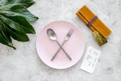 膳食结束 在板材附近的比尔、钱包和在灰色石台式视图的银行卡有横渡的匙子的和叉子 图库摄影