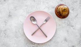 膳食` s 请求票据 在板材附近为在灰色石台式视图copyspace的响铃与横渡的匙子和叉子服务 图库摄影