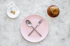 膳食` s 请求票据 在板材附近为在灰色石台式视图copyspace的响铃与横渡的匙子和叉子服务 库存图片