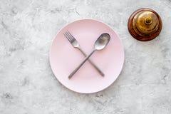 膳食` s 请求票据 在板材附近为在灰色石台式视图copyspace的响铃与横渡的匙子和叉子服务 免版税库存图片