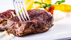 臀部的牛排 关闭招标在白色板材的烤牛肉肉有菜装饰的 免版税库存图片