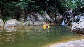 臂章游泳的母亲小女孩在瀑布的池塘 影视素材