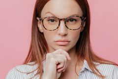 自信女性企业主接近的画象握下巴,抬眼眉,佩带光学玻璃,有黑发, 图库摄影