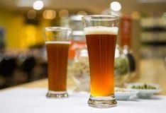 自创两个杯子在桌上的啤酒 库存照片