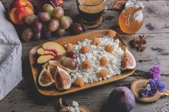 自创乳清干酪乳酪,莓,无花果,桃子,蜂蜜 健康早餐,咖啡 在土气木的服务板 库存图片