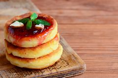 自创乳酪油炸馅饼 油煎的乳酪油炸馅饼用莓果果酱和杏仁在一块白色板材和在木背景 库存照片