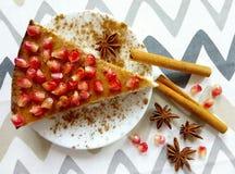 自创乳酪蛋糕用石榴和肉桂条和美洲黑杜鹃星 免版税库存照片