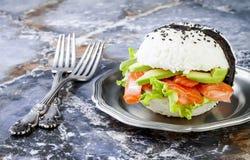 自创亚洲样式面筋免费寿司三文鱼汉堡 寿司食物杂种趋向 与拷贝空间的明亮的蓝色背景 免版税库存照片
