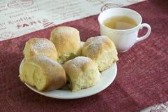 自创传统捷克小圆面包充塞用李子阻塞,葡萄干和酸奶干酪在白色板材在桌上用茶和flowe 库存照片