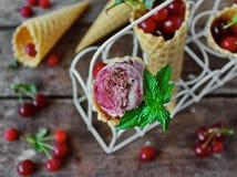 自创冰淇凌樱桃和巧克力在奶蛋烘饼锥体,新鲜的樱桃在老木桌上 库存照片