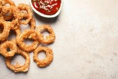 自创嘎吱咬嚼的油煎的洋葱圈和西红柿酱在轻的背景,顶视图 免版税库存照片