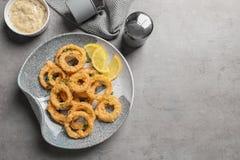自创嘎吱咬嚼的油煎的洋葱圈和调味汁在灰色背景,顶视图 免版税库存照片