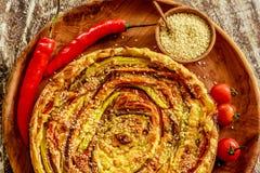 自创圆的菜饼服务用西红柿、辣椒和芝麻籽在一个木盘子在木桌 免版税图库摄影