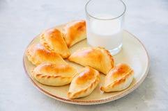 自创土豆充塞了与杯的empanadas在板材的牛奶 库存图片