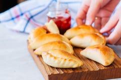 自创土豆充塞了empanadas用在一个木板的番茄酱 免版税库存图片