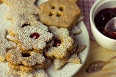 自创圣诞节和新年linzer曲奇饼用在一块白色板材搽粉的,果酱,关闭  免版税库存图片