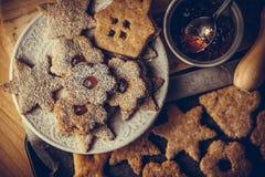 自创圣诞节姜饼和linzer曲奇饼用果酱,搽粉的,顶面平的看法,软的阴霾作用,葡萄酒 免版税库存照片