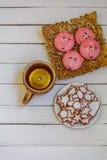 自创圣诞节曲奇饼,杯子茶用在白色木背景的柠檬 免版税库存图片