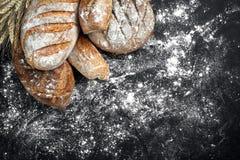 自创在黑背景的黑麦面包洒与面粉和各种各样的五谷和种子与麦子的小尖峰或 库存照片