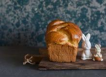 自创奶油蛋卷和陶瓷复活节兔子在一个土气切板 正面图 免版税库存照片