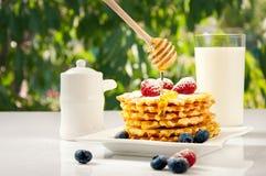 自创奶蛋烘饼用在板材的莓果在白色桌上 免版税库存照片