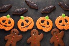 自创姜饼曲奇饼为以南瓜、姜饼人和棒的形式万圣夜在黑暗的具体背景 顶视图 免版税库存照片