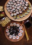 自创寿司卷 棍子,柠檬,酱油,山葵在一张黑褐色木桌上服务 免版税图库摄影