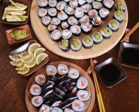 自创寿司卷 棍子,柠檬,酱油,山葵在一张黑褐色木桌上服务 库存照片
