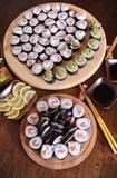 自创寿司卷 棍子,柠檬,酱油,山葵在一张黑褐色木桌上服务 图库摄影