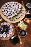 自创寿司卷 棍子,柠檬,酱油,山葵在一张黑褐色木桌上服务 免版税库存图片