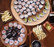 自创寿司卷 棍子,柠檬,酱油,山葵在一张黑褐色木桌上服务 免版税库存照片