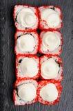 自创寿司设置了与红色tobiko和乳脂干酪在黑pla 免版税库存照片