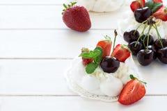 自创小pavlova蛋白甜饼结块与mascarpone奶油、草莓、樱桃和新鲜薄荷叶子 免版税图库摄影