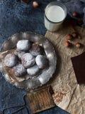 自创巧克力在搽粉的糖、巧克力曲奇饼与镇压和一杯卷曲牛奶 免版税库存图片