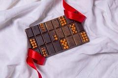 自创巧克力块 在白色纺织品背景的手工制造甜点 图库摄影