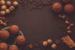 自创巧克力松饼用在棕色木书桌上的香料 免版税库存图片