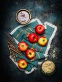 自创巧克力苹果的准备在做用热的液体巧克力、枝杈和切好的杏仁的棍子的 免版税库存图片
