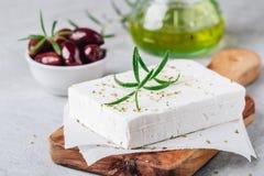 自创希腊乳酪希脂乳用迷迭香和草本在切板有橄榄油和橄榄的 库存照片