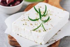 自创希腊乳酪希脂乳用迷迭香和草本在切板有橄榄油和橄榄的 图库摄影