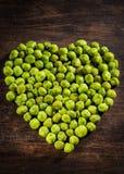 自创干香料山葵豌豆作为在心形的一道开胃菜在木背景 免版税库存照片