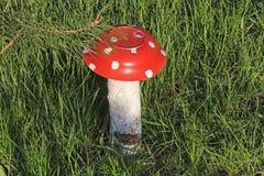 自创庭院雕塑-在草的蘑菇伞形毒蕈 蘑菇由一本老板材和日志被做 免版税库存图片