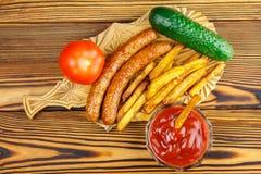 自创快餐,炸薯条的部分,番茄酱,烤了香肠,蕃茄,在木板的黄瓜 库存图片
