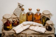自创手工制造香肠,酊 冬天库存在家在玻璃瓶子的罐头 在背景礼物盒的减速火箭,土气样式 免版税库存图片