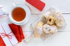 自创新月形面包用果子阻塞,装饰用与一个杯子的搽粉的糖早晨茶 库存照片
