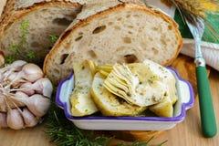 自创新鲜的意大利面包和朝鲜蓟在盐水用香料 库存照片